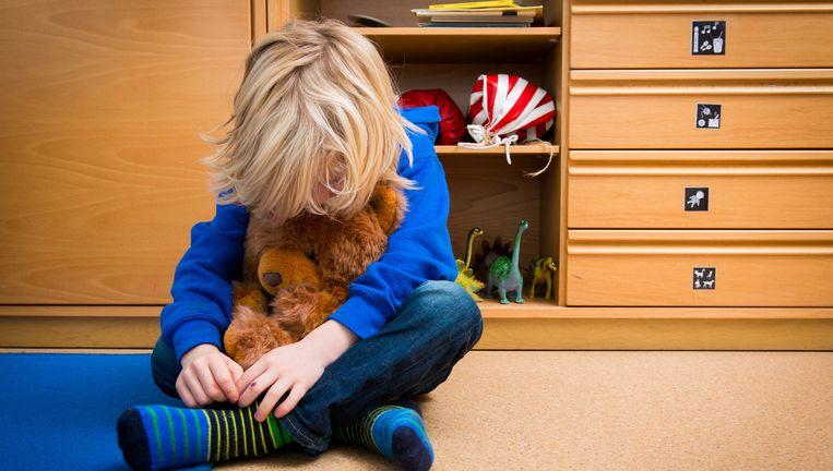 Een jongen met een knuffelbeer in een speelkamer van een jeugdhulpverleningscentrum. Beeld anp