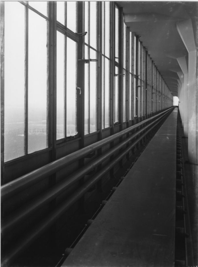 Transportband en buisleidingen langs de uit ramen bestaande buitenwand. Mét een weids uitzicht over de omgeving.