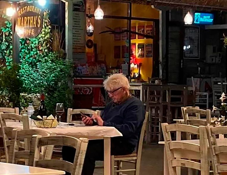 Stanley Johnson checkt zijn telefoon. Zijn vakantiekiekjes heeft hij inmiddels snel van Instagram verwijderd toen Griekse verslaggevers hem vertelden dat een Brit in deze coronatijd helemaal niet in Griekenland mag zijn.  Beeld AP