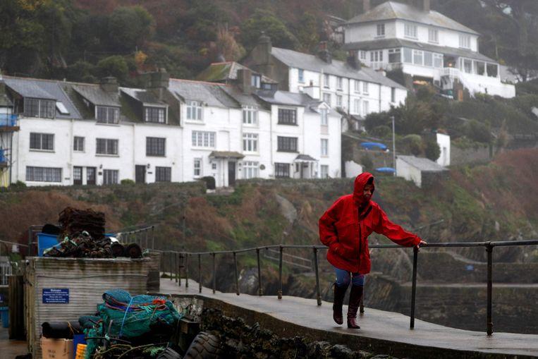 Een vrouw voelt de rukwinden in de vissershaven van het plaatsje Polperro in Cornwall, in het uiterste zuidwesten van Engeland.