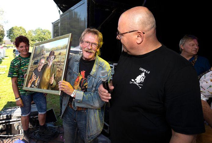 Henk Kelder krijgt tijdens de muzikale boekpresentatie zaterdag in Zelhem een schilderij.