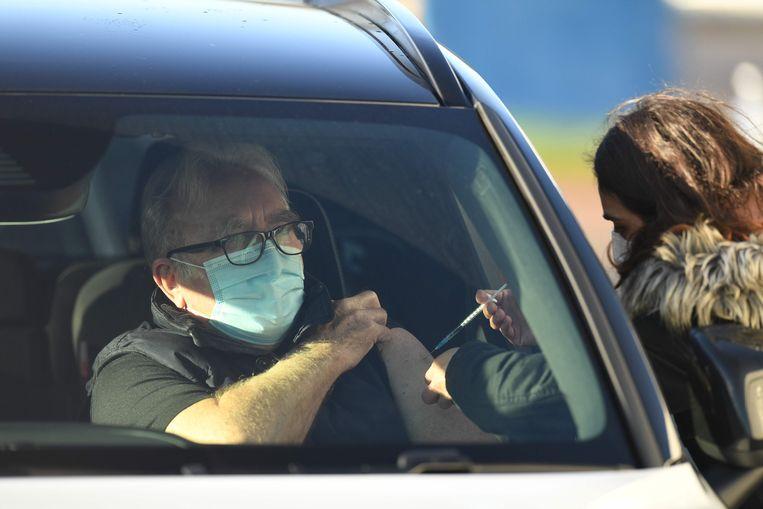 In Hyde, in Engeland, krijgen Britten een covid-prik bij een drive-in-vaccintatiecentrum.  Beeld AFP