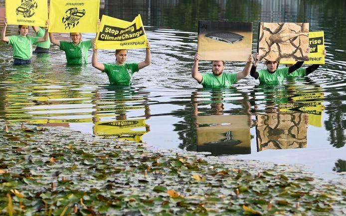 Activisten van Greenpeace tijdens hun protestactie in een meer tegenover het salongebouw.