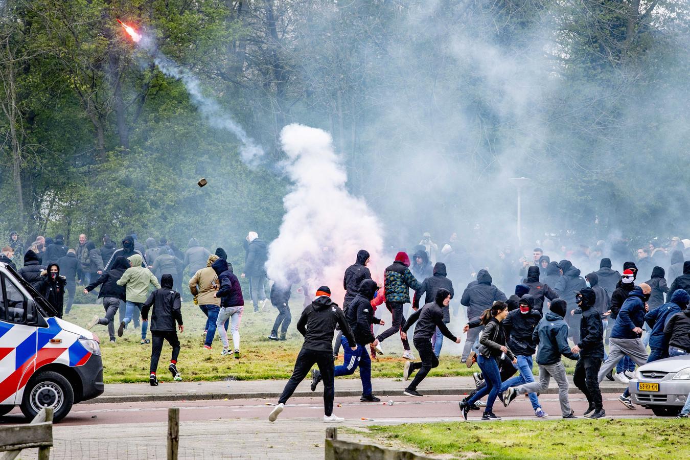 Feyenoord-fans bekogelen de politie met vuurwerk en stenen tijdens de laatste training van hun team voor de wedstrijd tegen Ajax.