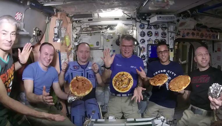 De Italiaanse astronaut Paolo Nespoli (midden) en zijn collega's met de in het ISS gebakken pizza's. Beeld null