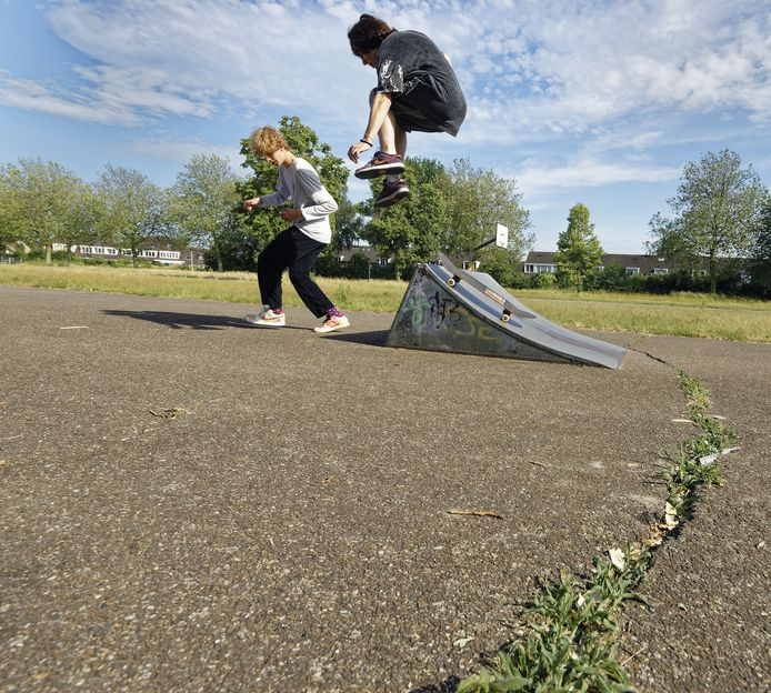 Joshua Tiebosch (rechts, hangend in de lucht) en Sam Voulon in actie op het skatebaantje in Haarsteeg. Op de voorgrond een van de scheuren in het asfalt. De schans zelfs is verbogen.