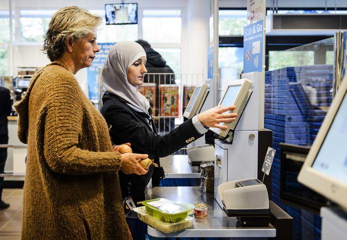 Een medewerker van de supermarkt helpt een klant bij de zelfscankassa. De foto is genomen voor het begin van de coronacrisis.