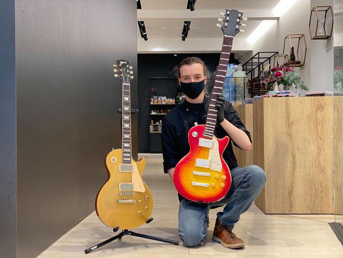 Stijn Vandenbouhede heeft de exacte replica in chocolade vast, links staat de echte gitaar.