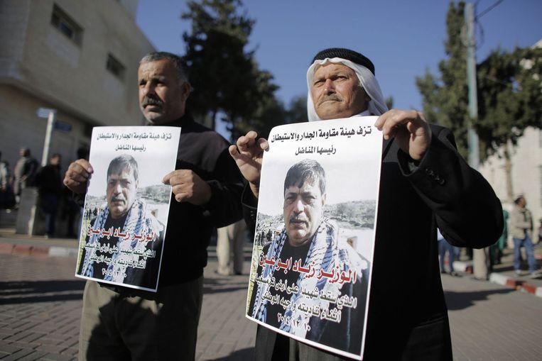 Mensen houden posters omhoog met daarop een foto van de overleden Palestijnse minister Ziad Abu Ein. Beeld reuters