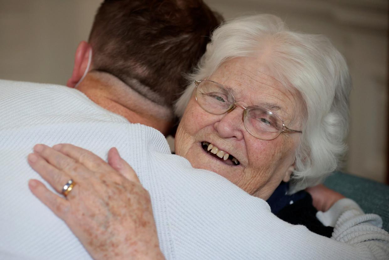Een Britse ouderenverzorger knuffelt een van de inwoners in een verzorgingstehuis in Londen op 17 mei 2021. Beeld Reuters