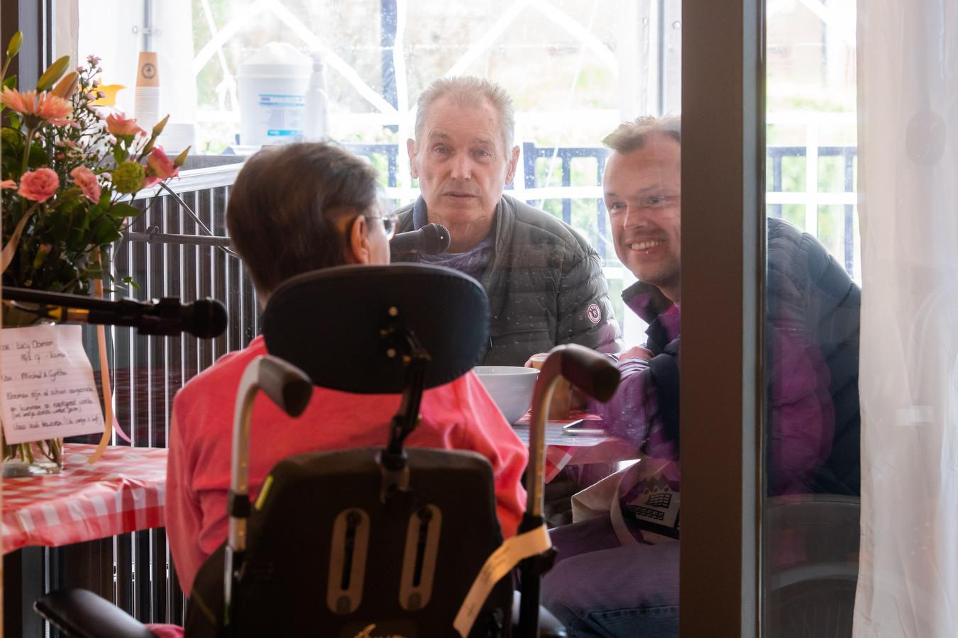 Jan en Michel Oomen bezoeken vanuit de tent Lucy Oomen. Met microfoons kunnen ze communiceren met glas ertussen.