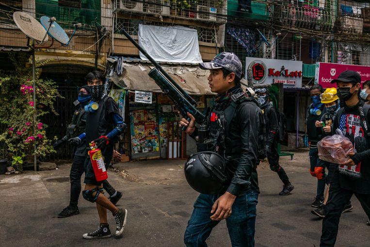 Demonstranten tegen de junta met geïmproviseerde wapens in Yangon. Beeld Getty Images