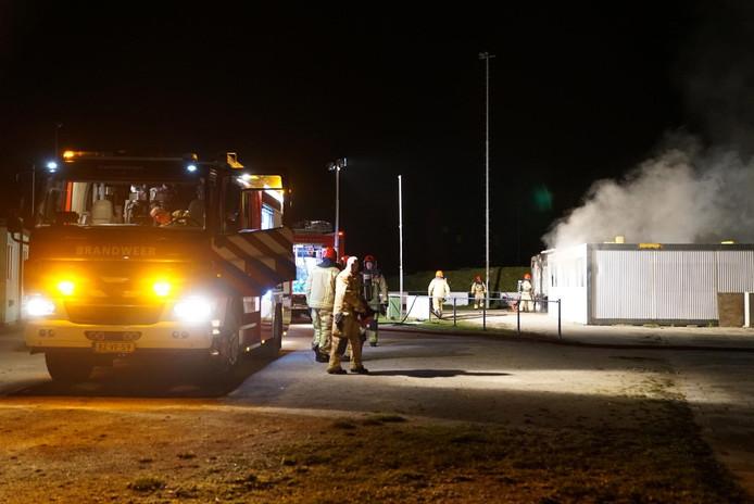 Brandweer bestrijdt het vuur tijdens brand bij FietsCrossVereniging Veldhoven.