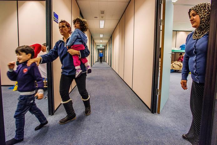 Mevrouw Ali staat in de deuropening, haar man komt richting hun nieuwe 'thuis' gelopen in het voormalige Belastingkantoor in Tilburg.