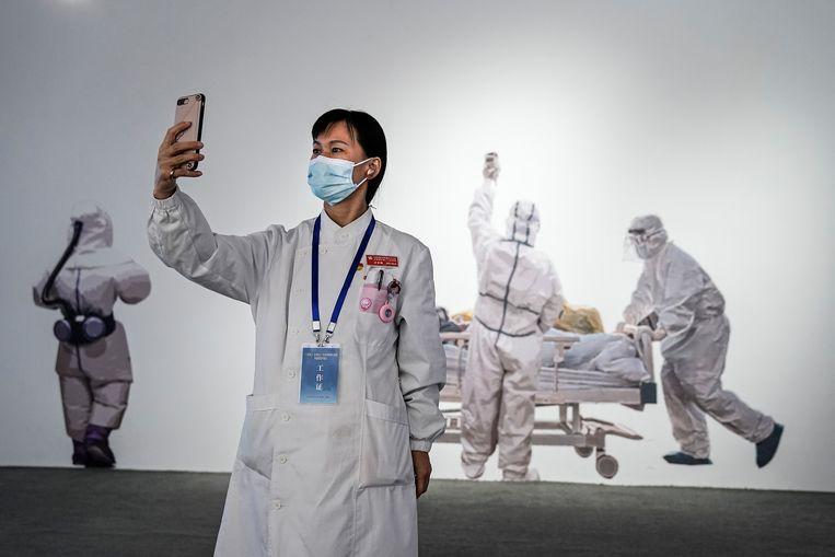 Een verpleegkundige neemt een selfie op een tenstoonstelling in Wuhan over de bestrijding van de coronapandemie. Beeld Getty