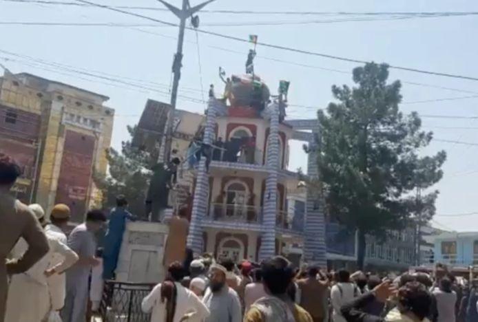 Bovenop een toren in Jalalabad wordt een vlag vervangen.