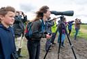 Suzan kijkt door de telescoop van de gids, Sybrand (links) heeft de regenwulpen al 'bestudeerd'.