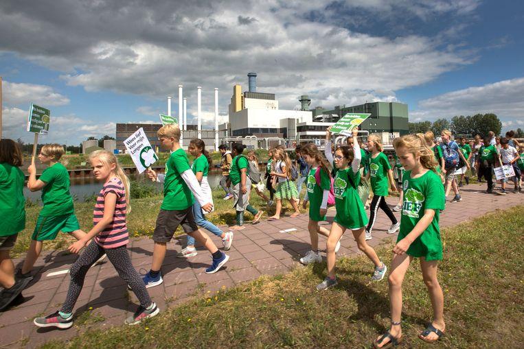 In een protestmars tegen de plannen voor een biomassacentrale lopen kinderen van Amsterdam-IJburg naar de bestaande elektriciteitscentrale van Vattenfall in Diemen. Beeld Maartje Geels