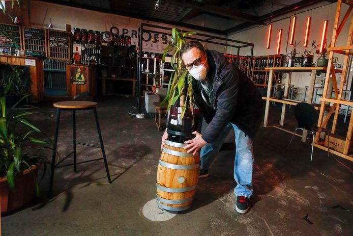 Eigenaar Mark Strooker laat door het verplaatsen van een plant zien welke rookschade er is in biercafé Oproer.