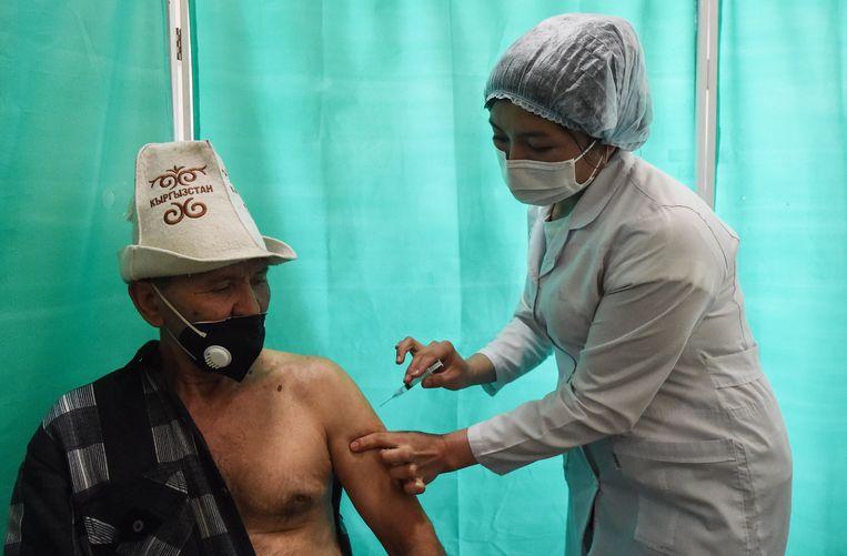 Een man krijgt zijn prik in de Kirgizische hoofdstad Bisjkek. Beeld AFP