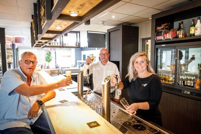 Stichtingsvoorzitter Henk Veldkamp (links) en David Apperlo van Slump Catering & Events  brengen een toost uit op de samenwerking met het  door Iris Lassche getapte biertje. Ze is straks pachter af, maar blijft met haar partner verbonden aan het zalencentrum.