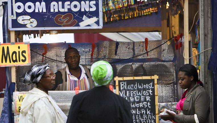 Een standhouder verkoopt Surinaamse delicatessen op de eerste dag van de 35e editie (2010) van het Kwakoe Zomerfestival in het Bijlmerpark in Amsterdam-Zuid-Oost. Beeld ANP