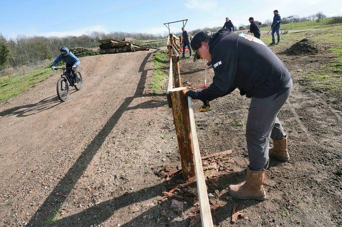Vrijwilligers zijn bezig - de zon schijnt net even - hekwerken te plaatsen op het bikepark in Mook.