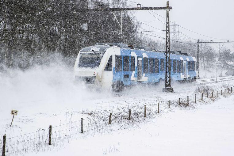 Een trein van vervoerder Keolis stuift voorbij in een besneeuwd landschap tussen Oldenzaal en Hengelo.  Beeld ANP