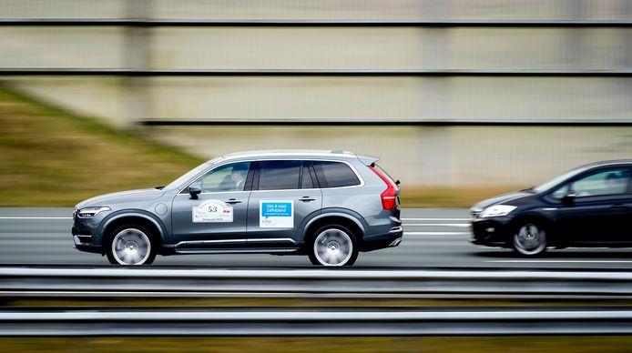 Een zelfrijdende auto over de A2 tussen het overige verkeer. In 2016 reden zelfrijdende auto's in treintjes van vijf als test achter elkaar.