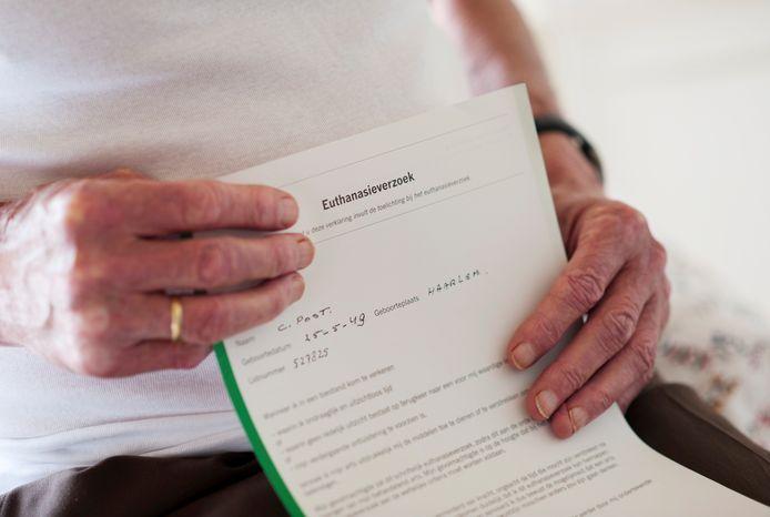 Een oudere heer houdt een wilsverklaring vast.