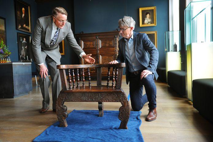 MuZEEum-directeur Onno Bakker gaat op de knieën voor de vierhonderd jaar oude kapiteinsstoel, die Jean-Marie van Isacker wil laten pronken in een tentoonstellingszaal.