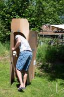 Frank van der Veen in een alternatief wc-huisje, gemaakt van een kartonnen doos.