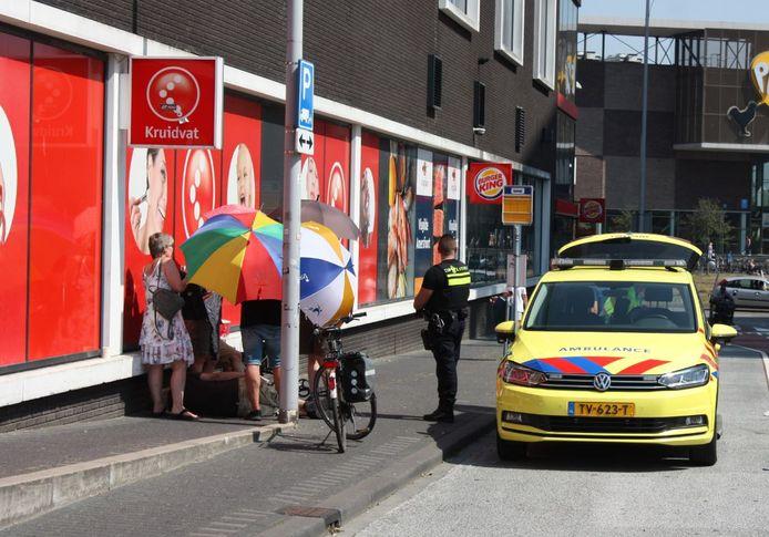 Omstanders beschermen de man met paraplu's tegen de zon