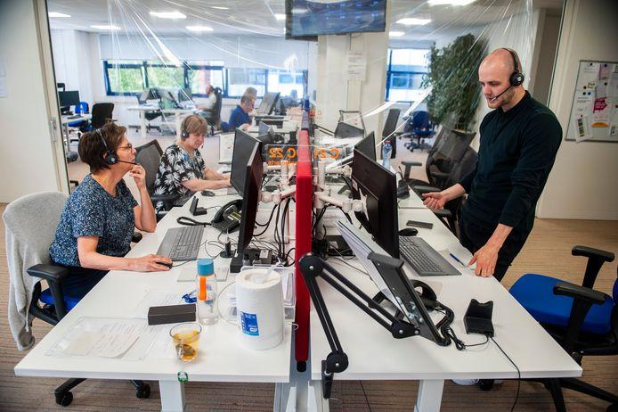 Een triagist van het triagecentrum van de huisartsenposten Oost-Brabant in Den Bosch vraagt de huisarts die tegenover hem zit om advies.