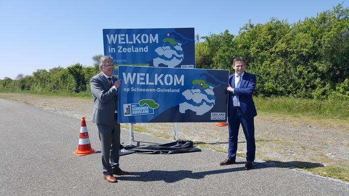 Burgemeester van Schouwen-Duiveland Gerard Rabelink (l) en gedeputeerde Jo-Annes de Bat onthulden de nieuwe welkomstborden van de provincie, gemeentes en VVV Zeeland.
