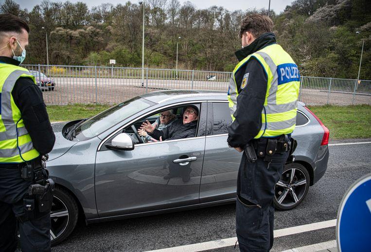 Nederlands echtpaar in gesprek met de Duitse politie. Ze moesten terugkeren naar Nederland, omdat ze geen geldig negatief coronatestbewijs bij zich hadden. Beeld Koen Verheijden