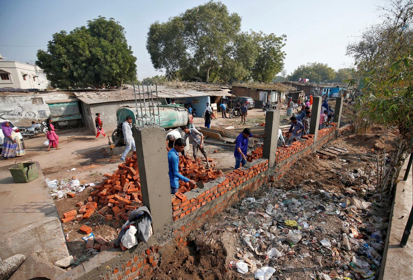 L'Inde construit un mur le long d'un bidonville.