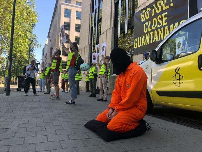 Uitgedost in een oranje gevangenistenue roept een Amnesty International-activist president Biden op om het detentiecentrum Guantánamo te sluiten.