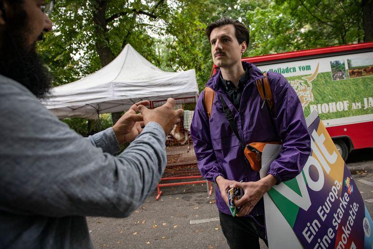 Paul Loeper discussieert met een kiezer in  de Kollwitzstrasse in Berlijn. Beeld Kerem Uzel