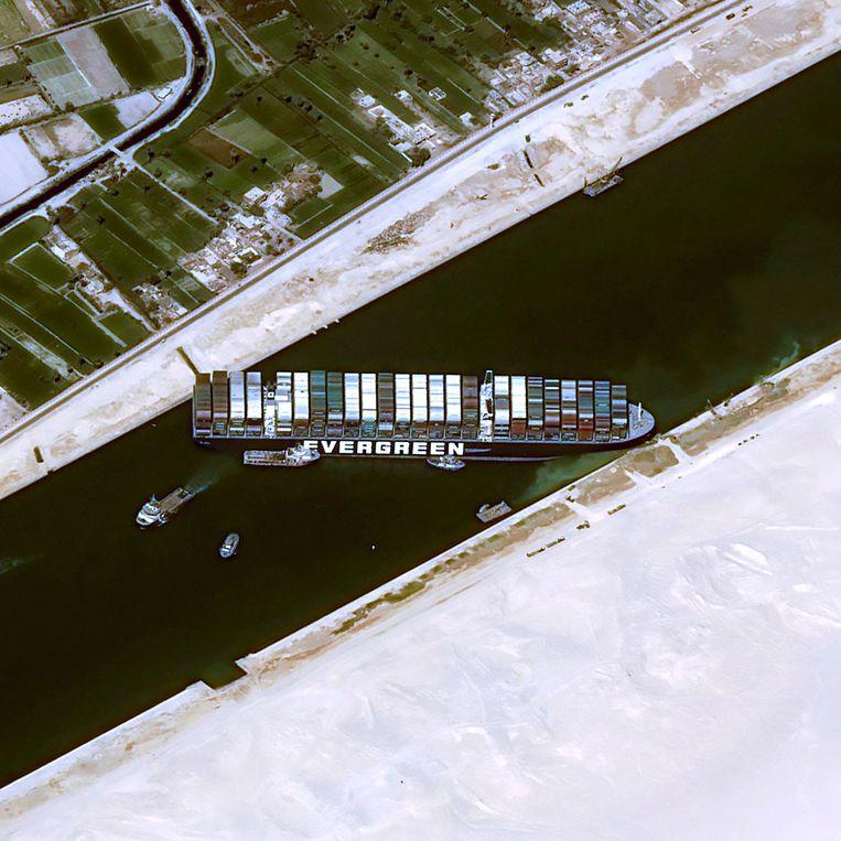 De voor- en achterkant van de Ever Given hebben zich helemaal in het zand van de oevers van het Suezkanaal geboord, waardoor er geen enkel schip meer kan passeren. Beeld AFP