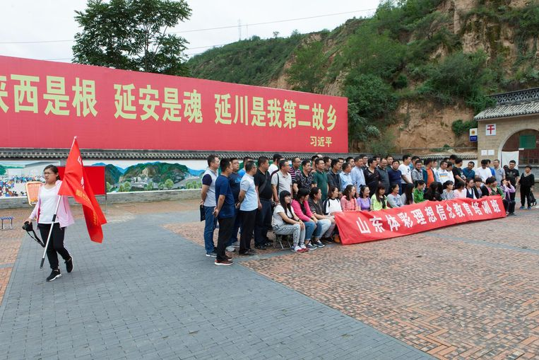 Een groep bezoekers aan Liangjiahe stelt zich onder een partijslogan op voor een groepsfoto. Beeld Foto Wassink Lundgren
