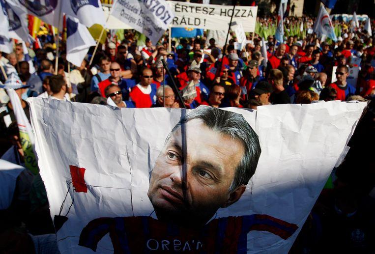 Een demonstratie in Boedapest tegen de Hongaarse regering, 1 oktober 2011. Op het spandoek het hoofd van premier Orban. Beeld REUTERS