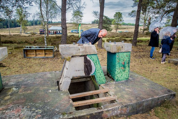 Loenen - IJkbasis Loenermark op de Zilvense Hei. Dit meetinstrument is vandaag officieel een Rijksmonument geworden. Genodigden bekijken in de regen het instrument.