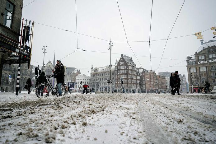 Een besneeuwde Dam in Amsterdam. Ook de hoofdstad is bedekt onder een dikke laag sneeuw.