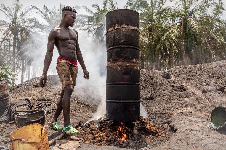 In het dorpje Mbonjo maakt een jongeman palmolie uit pitten geoogst uit zijn kleine palmboomgaard. Beeld Sven Torfinn