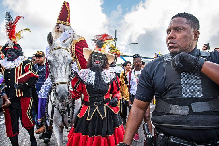 Sinterklaas komt aan op Otrobanda. Op Curaçao is de intocht een volksfeest waar iedereen aan meedoet. Rechts een beveiliger van de Sint. Beeld Guus Dubbelman / de Volkskrant