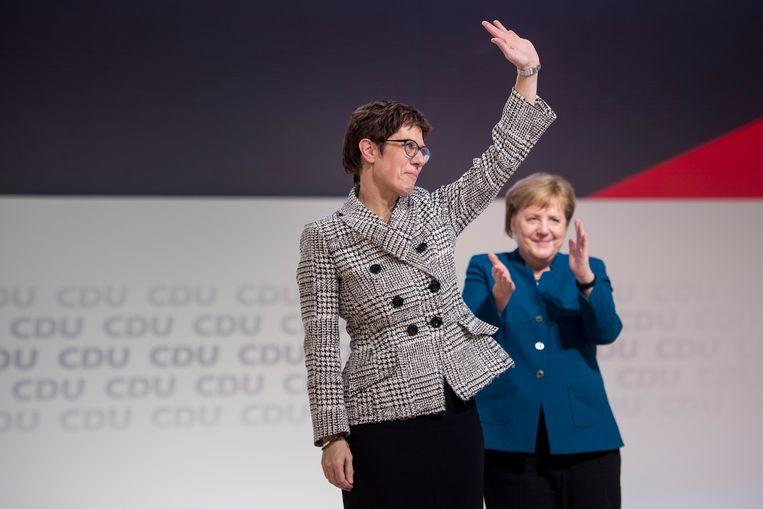 Annegret Kramp-Karrenbauer neemt op het podium het applaus van het congres in ontvangst als nieuw gekozen voorzitter van de CDU. Angela Merkel, nog wel bondskanselier, doet een stapje terug.   Beeld Thomas Lones / Getty Images