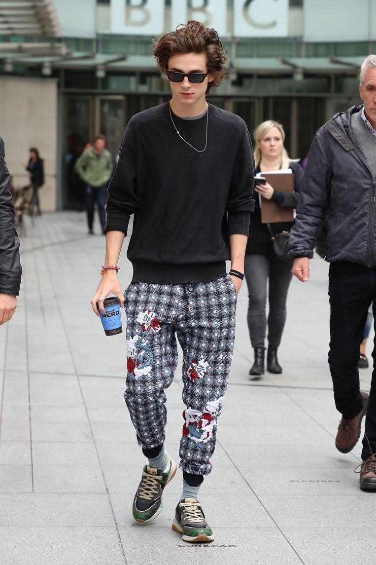 Chalamet haalt koffie in Londen in een Thom Browne-joggingbroek en Gucci-sneakers. Beeld Getty