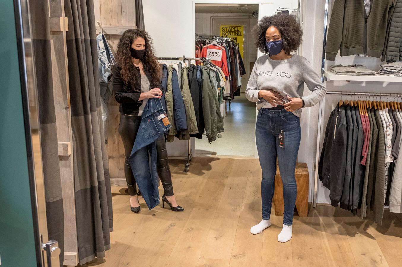 Verkoopmedewerkster Nancy Rutten (links) help Kasey Gordon met het passen van een broek.