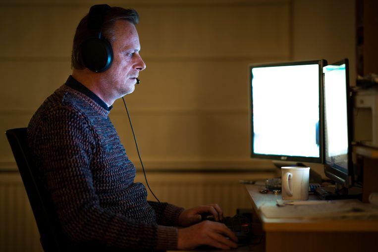 Erik Jaspers achter zijn bureau in zijn woning in Maastricht. Hij werkt als callcentermedewerker voor het minimumloon. Beeld Freek van den Bergh / de Volkskrant